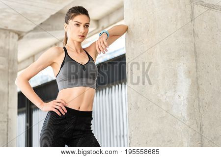 Now my figure is perfect. Portrait of confident female athlete standing and looking forward with self-assurance. She is wearing tracker on wrist. Copy space