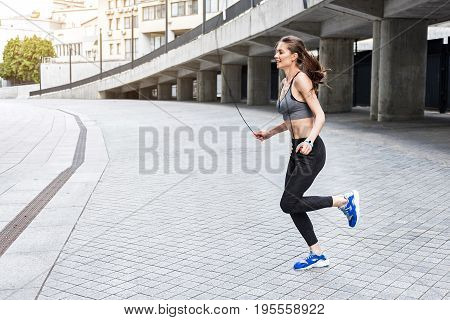 Side view of excited female athlete skipping on rope and smiling. She is exercising near stadium. Copy space