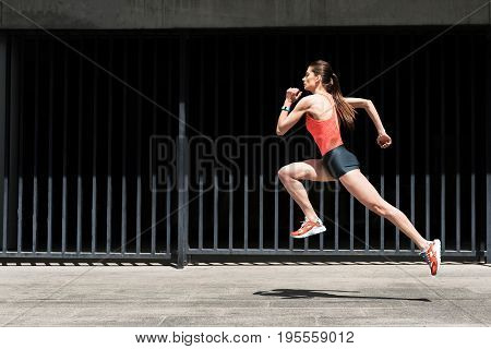 Life in motion. Cheerful girl is jumping while jogging with concentration outside. Power and speed concept