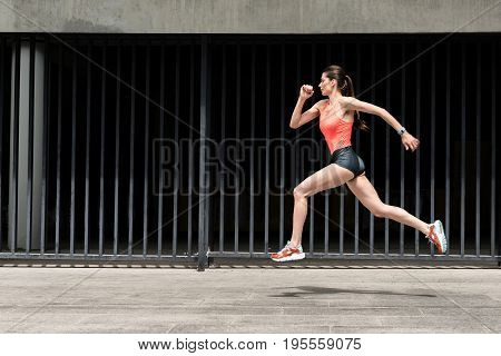 When you run, time stops. Fit young woman is jogging while jumping in the air and looking forward with confidence. Copy space in left side
