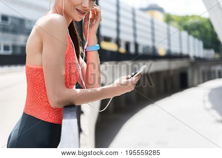 There is nothing more relaxing after hard training like music. Positive female athlete is wearing earphone and smiling. She is holding phone while standing on balcony. Copy space