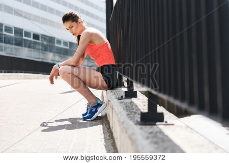 It was hard training. Side view of pensive tired young woman sitting on curb near fence outdoors. Copy space