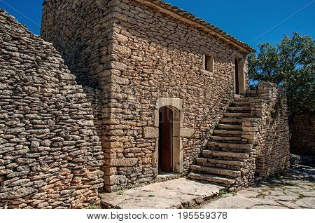 Typical house made of stone with staircase and sunny blue sky, in the Village of Bories, near the town of Gordes. Vaucluse department, Provence region, in southeastern France