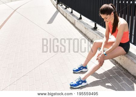 Top view of despaired female runner suffering from ache in joint. She is touching knee with frustration while sitting near road. Copy space