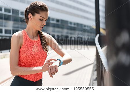 Serious young sportswoman is looking at tracker and checking her results. She is standing outdoor