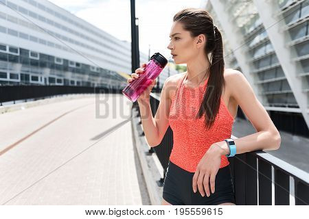Tired young woman is very thirsty after running. She is holding bottle of beverage and looking aside pensively while standing near stadium. Copy space in left side