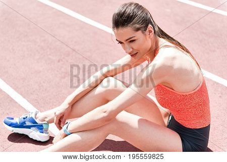 Dreamful young woman is resting after training. She is sitting on running track with relaxation and smiling. Portrait