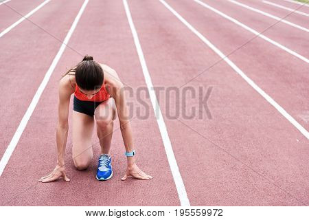 Serious young woman is concentrating before running. She is kneeling on stadium and preparing for start. Copy space in right side