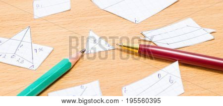 Pen and pencil lie on the table with cut out geometric figures on a wooden background