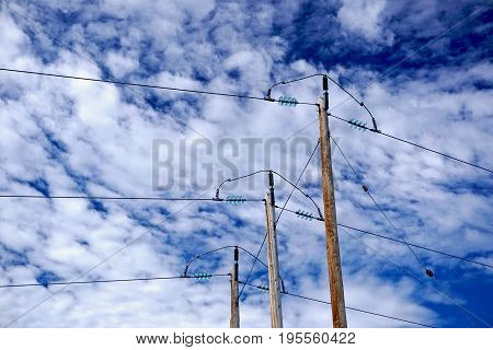 Wooden power poles against bright blue sky and white clouds