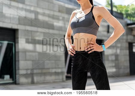 Fit and strong. Close up of slim female body. Young sportswoman is standing with arms akimbo on street. Copy space in left side