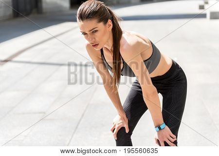 Portrait of tired young woman making break after running. She is standing and leaning arms on knees. Jogger is looking forward pensively. Copy space