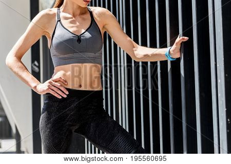 Close up of fit body of sporty girl standing with arm akimbo and touching face outdoors. Focus on her bare abdomen with press