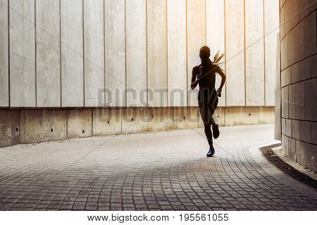Confident female jogger is training outdoors. Copy space in left side