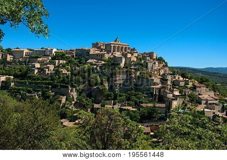 Panoramic view of the village of Gordes on top of a hill and under sunny blue sky. Located in the Vaucluse department, Provence region, in southeastern France