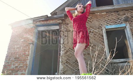 Beautiful girl lifestyle in red dress. Sexy girl in a dress is standing next to the old house of the ruins