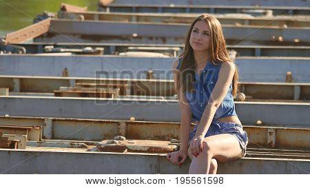 The girl is sitting on bridge. Sexy beautiful girl sits lifestyle on the bridge outdoor