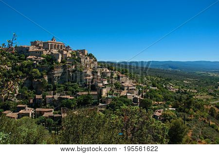 Panoramic view of the village of Gordes on top of a hill and under sunny blue sky. Located in the Vaucluse department, Provence region, in southeastern France.