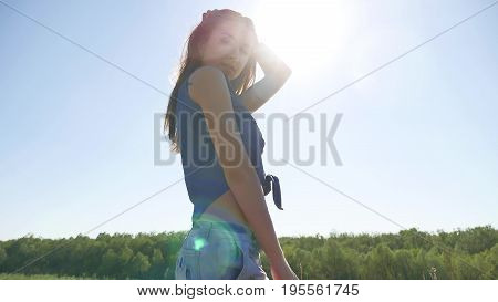 Sexy beautiful girl. Beautiful girl in denim shorts summer nature travel in wind sunlight lifestyle