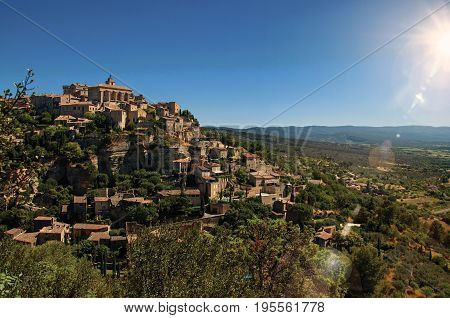 Panoramic view of the village of Gordes on top of a hill and under sunny blue sky. Located in the Vaucluse department, Provence region, in southeastern France. Retouched photo