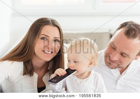 Happy Family Of Three  Is Enjoying At Home. Beautiful Baby Girl Playing With Cell Phone. Family Valu