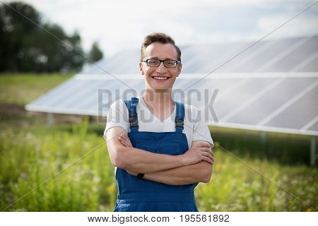 Worker standing in the field with solar with solar panels on backstage. Young man in glasses standing with his hands crossed.