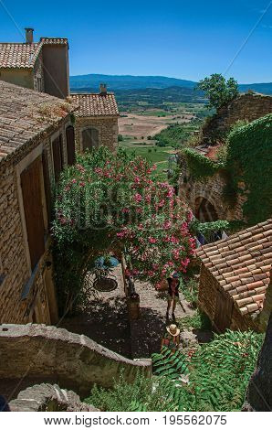 Gordes, France - July 03, 2016. Panoramic view of fields and hills of Provence, stone houses and flowering trees in Gordes. Located in the Vaucluse department, Provence region, southeastern France