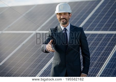 Businessman at solar energy etation holding hand. Man in suit standing ready for handshake.