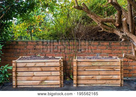Two wooden compost bins in a back garden.