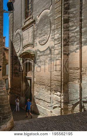 Gordes, France - July 03, 2016. View of alleyways in the historical city center of Gordes, with shops in front and church in the background. Vaucluse department, Provence region, southeastern France