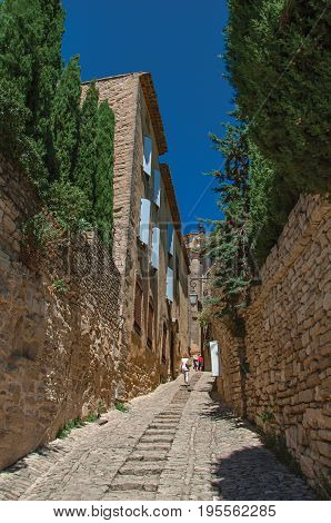 Gordes, France - July 03, 2016. Typical stone houses with sunny blue sky, in an alley of the historical city center of Gordes. Located in the Vaucluse department, Provence region, southeastern France
