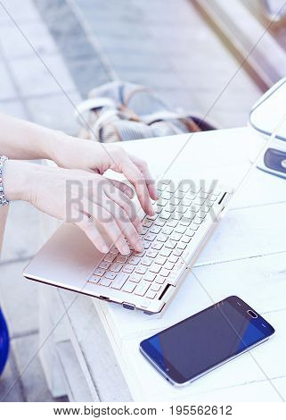 Unrecognizable young woman working on laptop and typing on the keyboard outdoors, selective focus