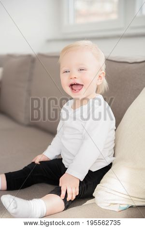 Nicely Dressed And Happy Baby Girl With Blue Eyes Sitting On The Sofa.