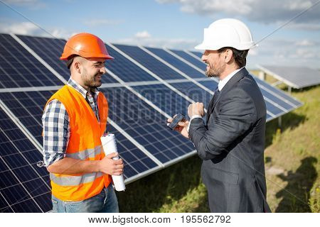 Business client showing photovoltaic detail to foreman. Solar energy station in the field, worker ond order comminicating.