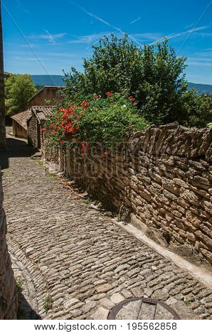 Gordes, France. View of typical stone houses and wall with sunny blue sky, in alley of the historical city center of Gordes. Vaucluse department, Provence region, southeastern France