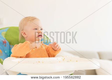 Portrait Of Adorable Baby Girl With Blue Eyes Sitting In The Highchair And Have A Lunch.