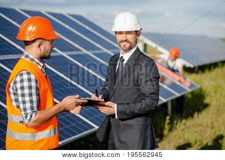 Signing of an agreement at solar energy station. Business client and foreman on front view and worker checking solar panels at backstage.