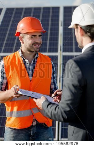 Business client signing contract for installation of solar power panels. Worker in orange helmet and vest holding folder with documents for clients signature.