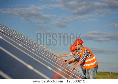 Engineers maintaining solar panels in the field. Control and service of photovoltaic panels.