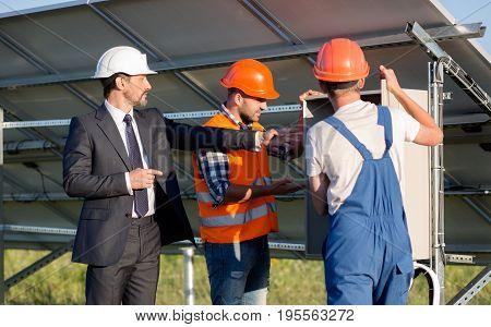 Business client and two employees looking at electrical box. Director asking to show electrical box.