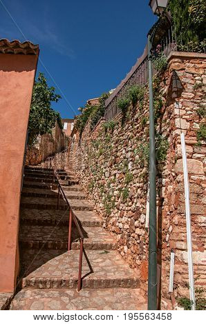 View of traditional colorful houses in ocher and stone staircase under a sunny blue sky, in the city center of the village of Roussillon. Vaucluse department, Provence region, southeastern France