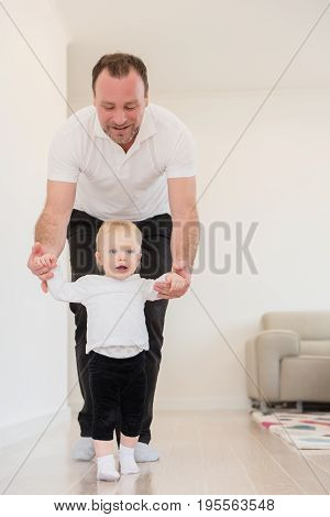 Happy Family Enjoying At Home. Father And His Beautiful Baby Girl Playing And Learning How To Walk.