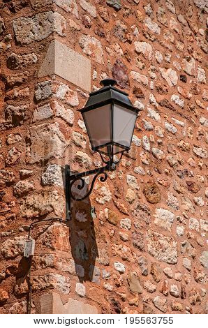 Close-up of lamp stuck in stone wall in sunny day, in the city center of the village of Roussillon. Located in the Vaucluse department, Provence region, southeastern France