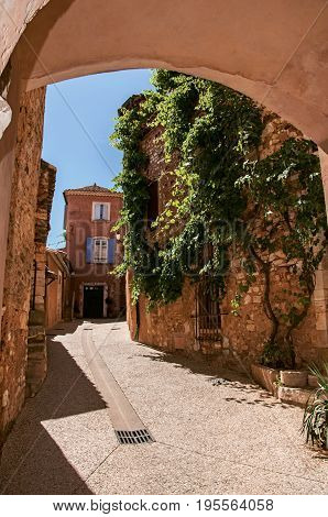 Roussillon, France - July 03, 2016. Traditional colorful houses in ocher under a sunny blue sky, in the historic Roussillon. Located in the Vaucluse department, Provence region, southeastern France