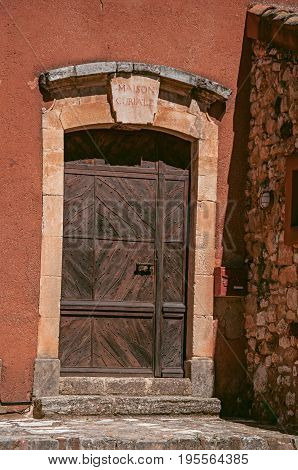 Roussillon, France - July 03, 2016. View of traditional colorful house door in ocher and wooden door, in the historic Roussillon. Located in the Vaucluse department, Provence region, southeastern France