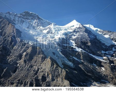 A snow covered mountain peak in rural Switzerland against a blue sky.