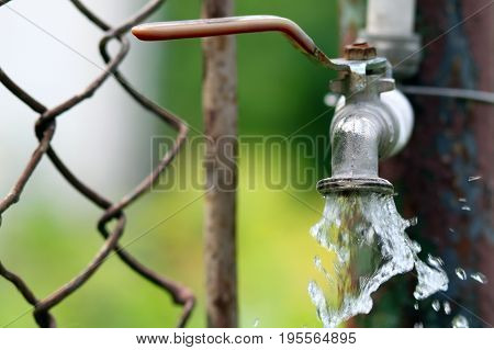 Close up of grunge brass faucet on green bokeh background. Water shortage and earth day concept.