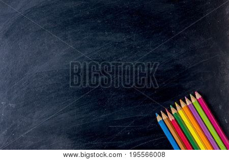 Bottom Of Colorful Pencil Crayons Against A Blackboard Background, Crayons Is A Supplies And Station