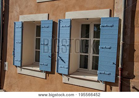 Roussillon, France - July 03, 2016. Detail of windows with blue shutters at sunset in the city center of the village of Roussillon. In the Vaucluse department, Provence region, in southeastern France