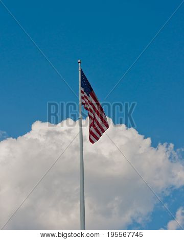 American Flag flying with clouds in the background
